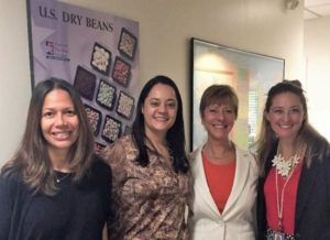 Standing in front of a US Dry Beans poster at the USDA Office in Sao Paulo, left to right: Fabiana Fonseca (USDA Agriculture Specialist), Gabriela Meucci (USDBC Brazil Consultant/Representative), Ellen Levinson (USDBC International Representative for the Americas and Emerging Markets), Chanda Berk (FAS Sao Paulo)